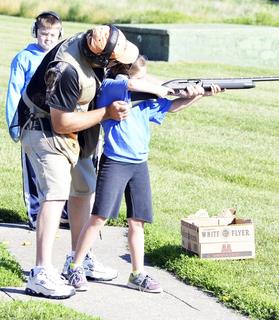 The instructor helps Hilary Lilard of Burlington steady her gun before shooting at targets. Photos by Jerry Morris