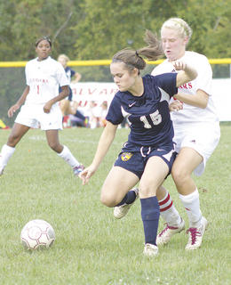 Lady Braves senior Emily Tillman fights off a Calvary Christian player for the ball Sept. 9 in Covington.