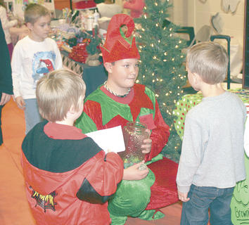 Derek Cummins dresses as an elf as he talks to elementary students anput gifts they can buy during the WMS eighth grade Entreprenuer Fair.