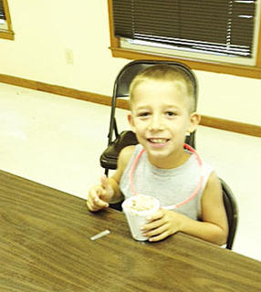 Ethen Webster eats his ice cream that he made at the Cloverbud Camp held on June 27 and June 28.