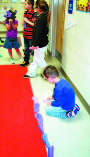 Brayden Taylor at Sherman Elementary lays out 100 feet cut from construction paper.