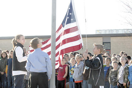 WES student council members Rachel Justice,  Bryce Montgomery, Brady Montgomery and James Alger work to raise the flag during a Veterans Day ceremony.