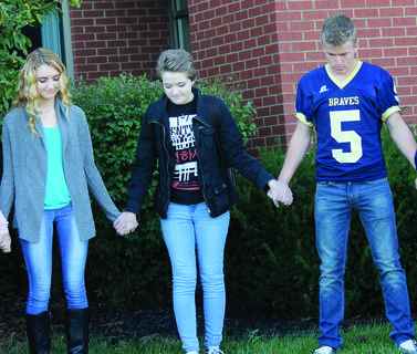 Riley Richardson, left, and Cody Wells pray with Abi Eakins as she speaks up with prayers to God for their school and student body.