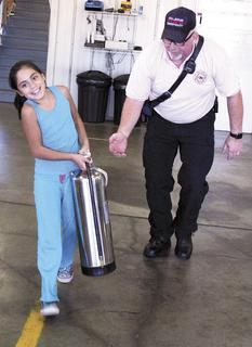 Jay Howard of the DRFD, encourages Briceyda Valdovinos as she carries a fire extinguisher through the obstacle course.