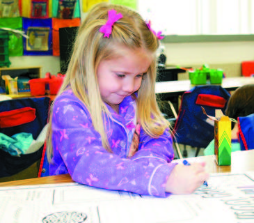 Kayla Adkins, a kindergarten student at Dry Ridge Elementary colors a 100 days poster.