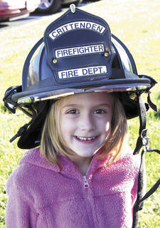 Sherman Elementary student Charlotte March tries on a Crittenden Fire Department helmet during Fire Prevention Week.