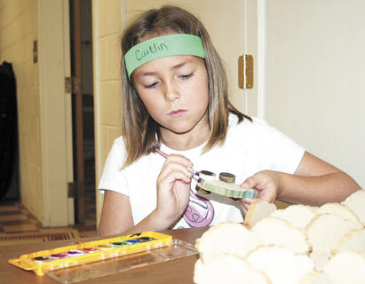 Caitlin Ousley concentrates on painting a sheep during the Vacation Bible School art activities. 