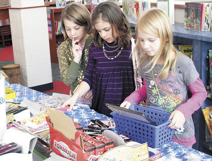 Sherman Elementary students Chloe Kinman, Ashley Byrd and Jessica Code shop at the school's Santa Shop.