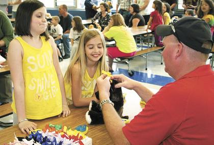 Sydney Parker and Morgan Asher get some help from Greg Hearn of the Dry Ridge Fire Department.