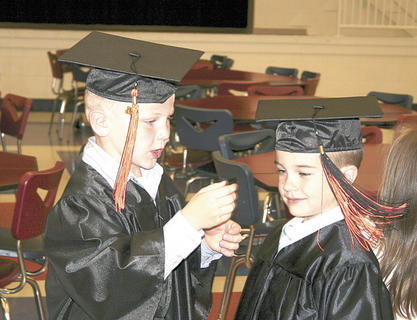 Adam Beck swings classmate Gunner Fagan's tassle as they wait to receive their diplomas.