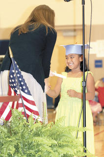 Leslie Rodriguez smiles as she is handed her diploma.