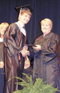 Steven Bradford smiles for the camera as board member Donna Cheesman hands him his diploma.
