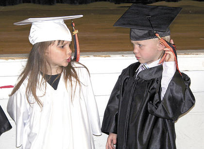 Olivia Spare, left, makes sure Isaiah Spencer leaves his cap alone.