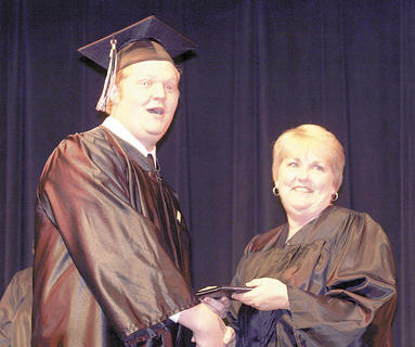 Jacob Siedenberg smiles enthusiastically as Cheesman hands him his diploma.