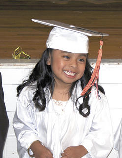 America Mendez smiles after putting on her cap and gown.