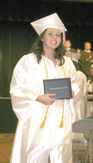 Taylor Stith walks the aisle with diploma in hand.