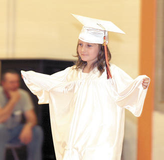 Sydney Ballard opens her arms like an angel as she walks to receive her diploma.