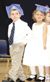 Kaden King, left, and Isabelle Lillpop, right, look for family as they walk into graduation.