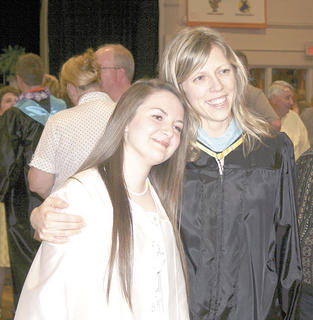 Brittany Hoskins shares a moment with teacher Paradise Forbes after graduation.