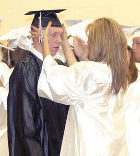 Josh Cook gets help from Sammi Pendleton putting on his cap.