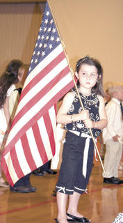 Addyson VanHolten holds the American flag before the kindergarten graduation begins.
