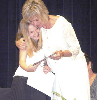 Katelyn Kidwell gets a hug from her teacher Trish Merritt as she receives her certificate.