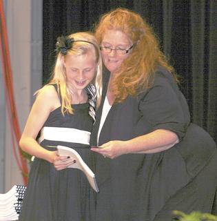 Shelby Gutman receives her certificate from teacher, Marcia Walters.