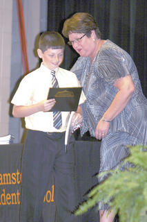 A.J. Scroggins receives his certificate from teacher, Debbie Popham.