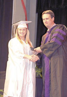 Alex Trumbo shakes board member Pete Whaley's hand as she receives her diploma.