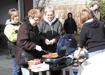 Karen Williams, Joni Eldridge, Amanda Faulkner and Emily Prewitt, from Northern Kentucky, grilled hot dogs for residents and workers on March 3. The women came to help their cousin, Kevin and Kelly Sears, residents of Harvester's Subdivision.