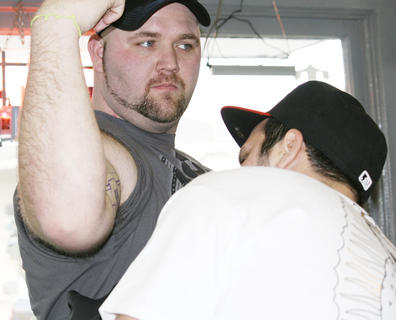 Tommy Maines gives a customer a hammer tattoo.