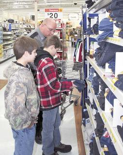 Williamstown Police Assistant Chief Chris Hankins helps pick out shoes during the Shop With a Cop program.