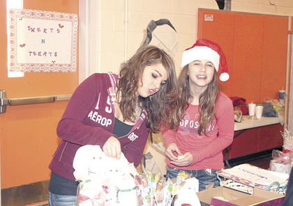 Kristine Robinson, left, and Amber Perkin, right, make hot chocolate to sell at their booth during the eighth grade Entreprenuer Fair.