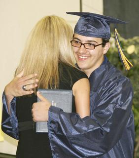 Austin Beard-Ruth gives Principal Claudette Herald a hug as he leaves the stage.