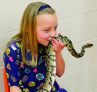 Left, Mandy Dodd gives the ball python a kiss during her meet-and-greet with Zoodles.