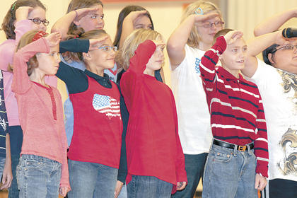 Members of the Williamstown Elementary School choir salute after singing during a Veterans Day assembly.