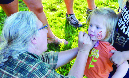 A volunteer paints Leah Wilson's face. Williamstown's annual Ice Cream Social is sponsored by local merchants.