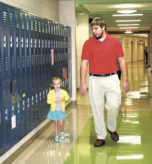 Sherman Elementary teacher Derek Haley walks kindergartner Virginia Conner down the hall and to her room during the first week of school. Photo by Jamie Baker-Nantz