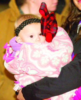Raine Kennedy stays bundled up while with a blanket and a bow.