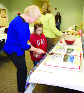 Librarian Melissa Wallace cuts Jesstina Monson a piece of cake.