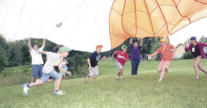 Dominick Tapp runs under the parachute wth Micah Elder, Anna Funk and Gillian Curtis.