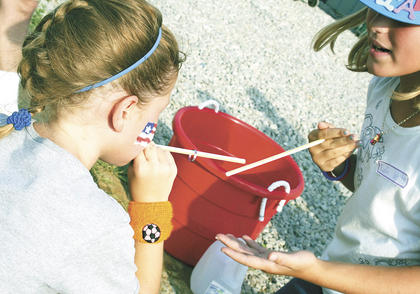 Ella White works hard to keep the ring on the straw and pass it to Lydia White.