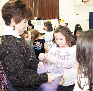 Dorothy Ryan holds a bucket while Jenna Ruber dumps her coins from a plastic bag.