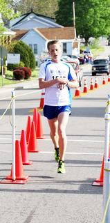 Tyler Edmondson crosses the finish line. Edmondson ran the 5K in 17.16. He was the overall race winner.