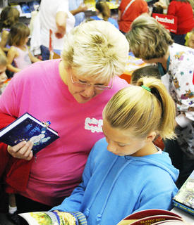 Diane Bierman and her granddaughter, Chole Kinman look at a book together.