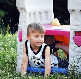 Ashton Neer has a good time while climbing out of the bottom of the playhouse.