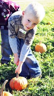 MCE student Logan Stites has a hard time picking up his pumpkin off the ground. 