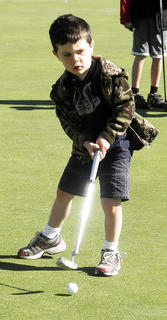 Louis Schlosser attempts to swing and hit the ball in the cup.