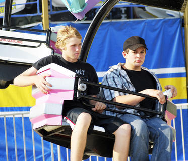 Dustin Smith and Jacob Fryman catch a breeze as they ride the Super Trooper, one of the rides at the Grant County Fair.