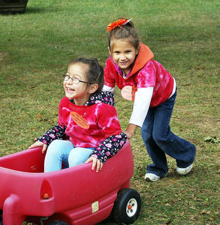 SES student Deslynn Nickell gives her friend Danica Cole a push in the wagon.